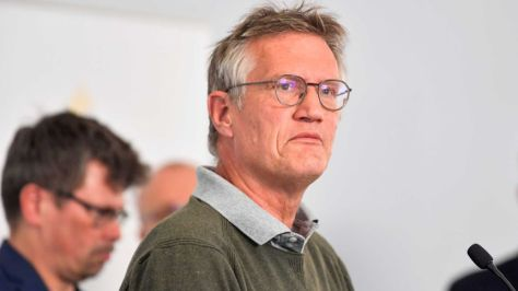 Anders Tegnell, wearing a grey collared shirt and dark-rimmed glasses, frowns slightly