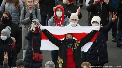 Belarusian opposition supporters hold a white and red flag during a protest in Minsk