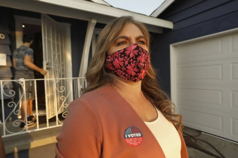 A woman with a face mask and I Voted sticker