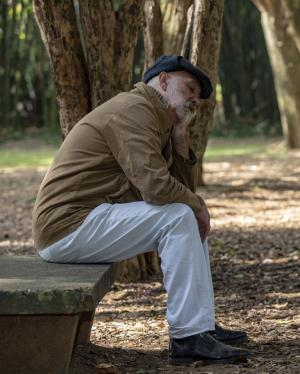 Tired older man on park bench