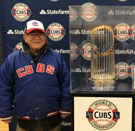 "Venustiano ""John"" Castañeda stands next to the World Series trophy."