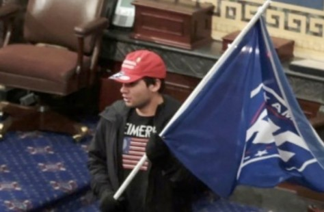 A man in a video still holds a flag in the Senate chambers