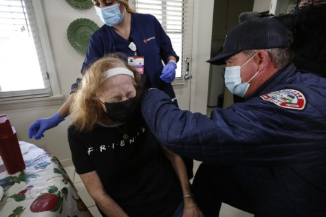 A woman wearing a mask cringes as she is vaccinated