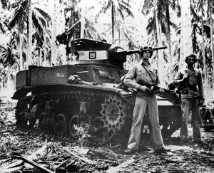 Nov. 4, 1942: Two alert U.S. Marines stand beside their small tank on Guadalcanal in the Solomon Islands during World War II. The military tank was used against the Japanese in the battle of the Tenaru River during the early stages of fighting. (AP Photo)