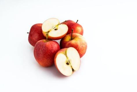 A white background on which sits 5 apples. 4 are whole and one has been cut in half to show the insides.