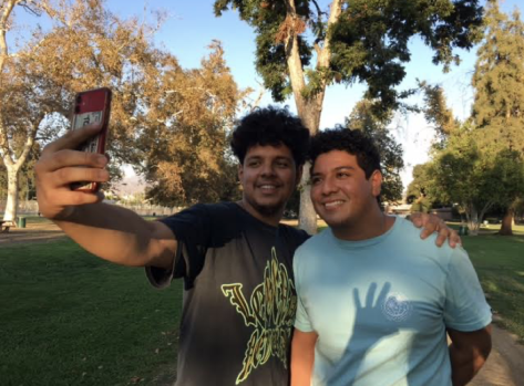 Two young men pose for a selfie amid trees in a park.